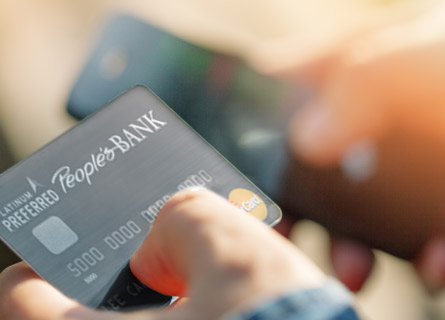 Person holding a People's Bank card in one hand and mobile phone in the other
